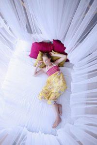 Endormie à l'abri d'une moustiquaire
