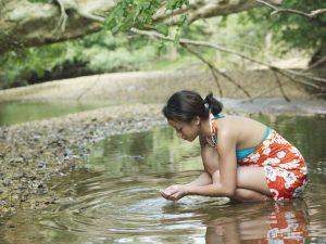 Femme buvant à la rivière